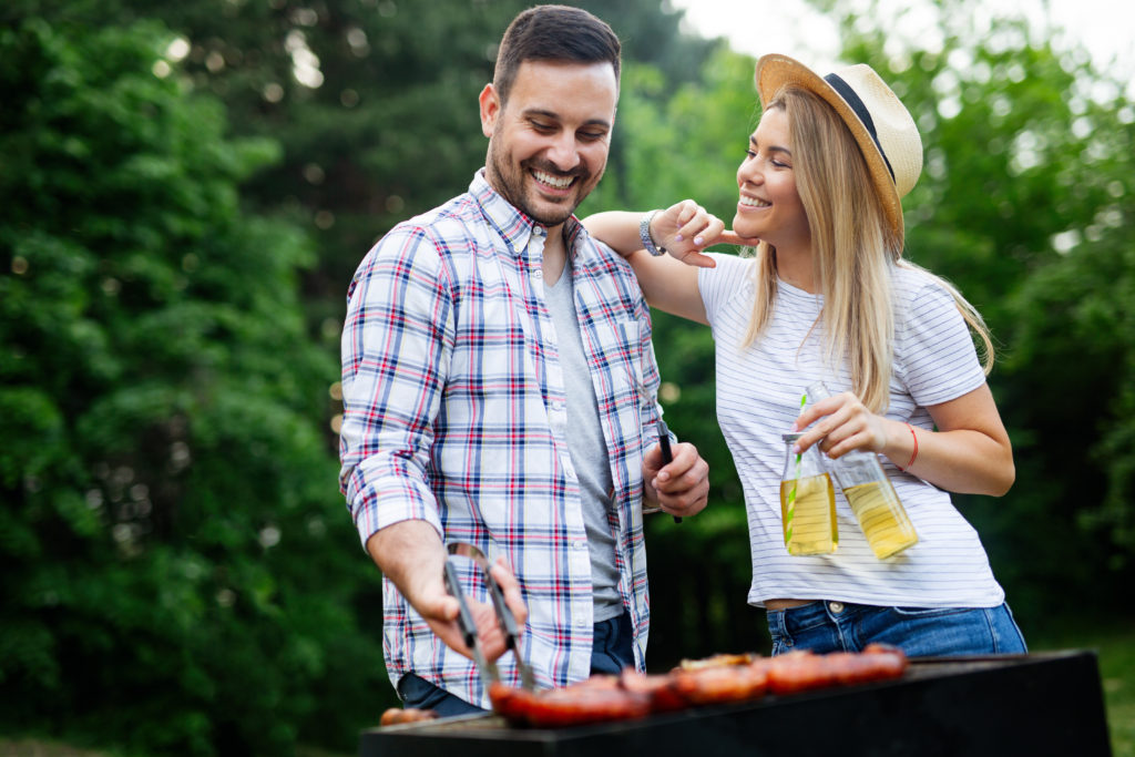 young couple preparing sausages on a barbecue outdoors