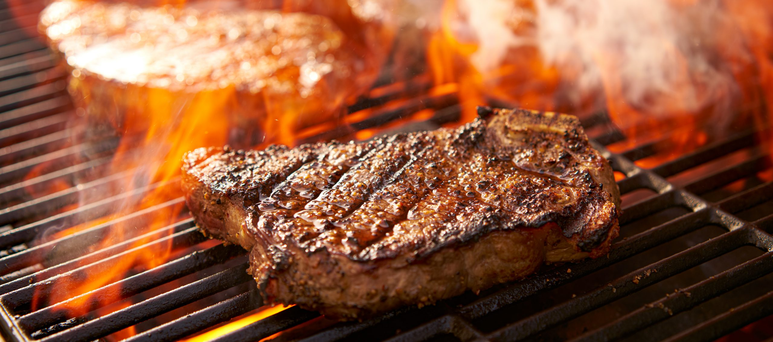 rib eye steaks cooking on flaming grill panorama